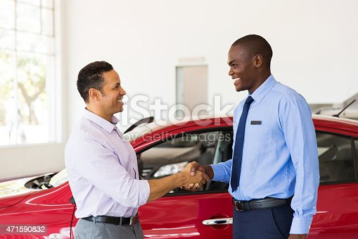 istock african american car dealer handshake with customer 471590832