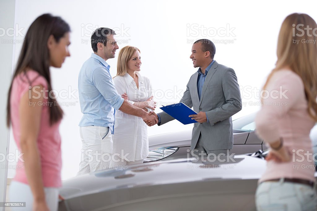 African American car sales person shaking hands with costumer. stock photo