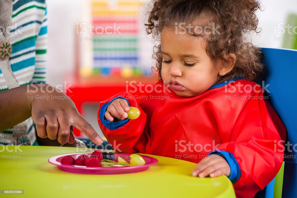African American Carer Encouraging Toddler During Her Meal stock photo