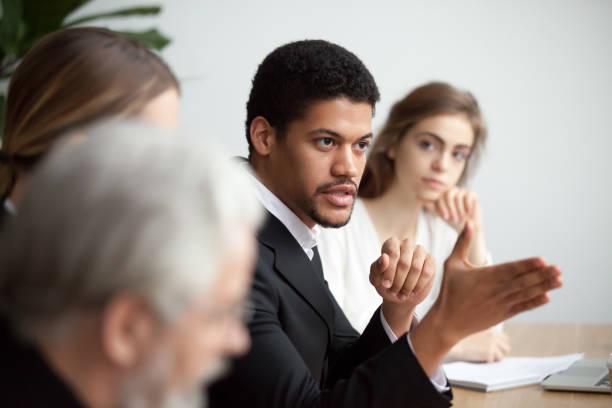 Afro-américaine PDG parle donnant des instructions à la réunion de l'équipe diversifiée - Photo