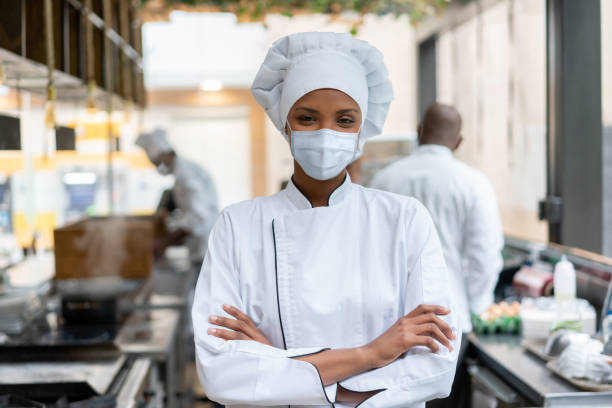 African American chef working at a restaurant wearing a facemask stock photo