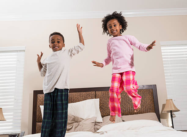 African American children having fun jumping on bed stock photo