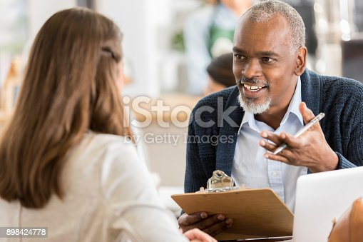 Cheerful senior man gestures as he interviews a young woman for a position in his coffee shop. He is holding a clipboard.