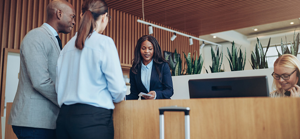 Young African American concierge working behind a reception counter helping two guests check into her hotel