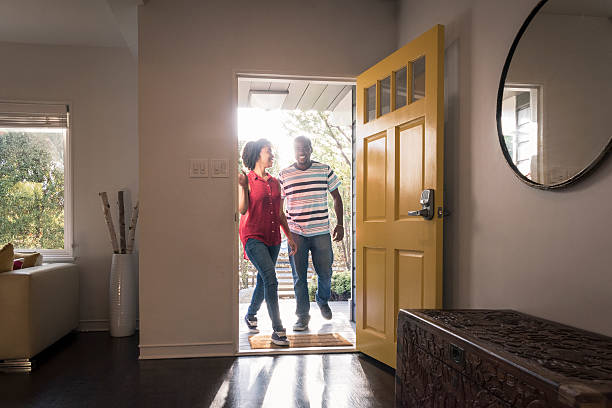 African American couple arriving home in doorway, smiling Young man and woman stepping into the house, they are happy and smiling as they come through the open yellow door front door stock pictures, royalty-free photos & images