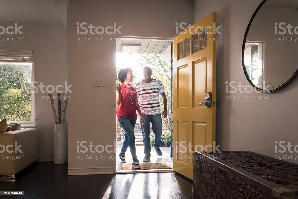 African American couple arriving home in doorway, smiling - foto de acervo
