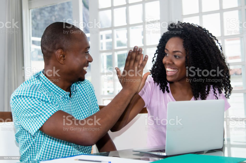African american couple at laptop give high five stock photo