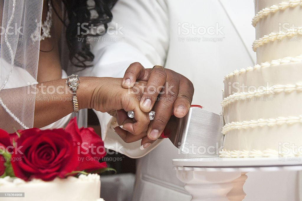 African American couple cutting white wedding cake with red roses stock photo