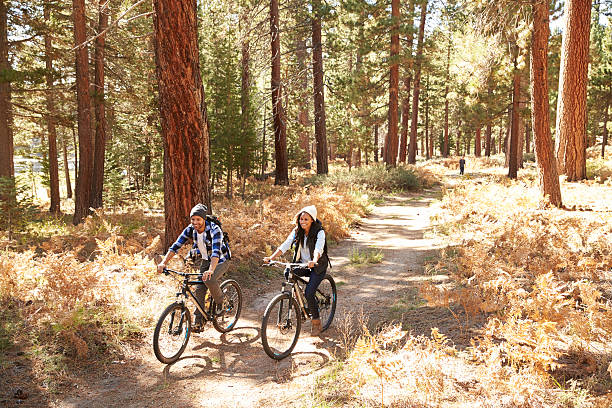 African American Couple Cycling Through Fall Woodland stock photo