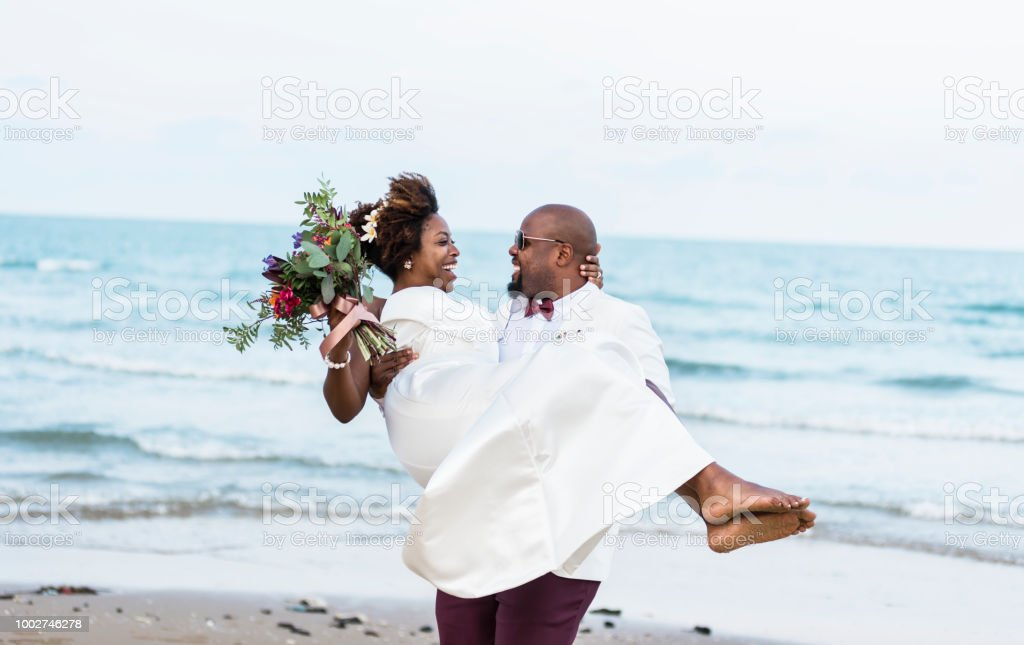 African American couple getting married at the beach stock photo