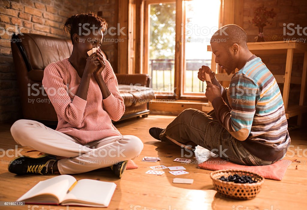 African American couple having fun while playing cards at home. stock photo