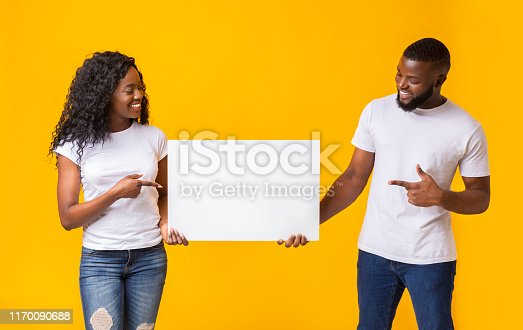 1168002879 istock photo African american couple holding white advertising board 1170090688