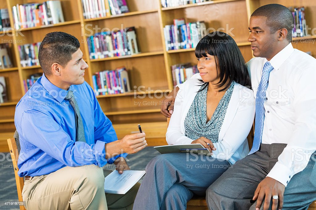 African American couple listening during marriage counseling session with therapist stock photo