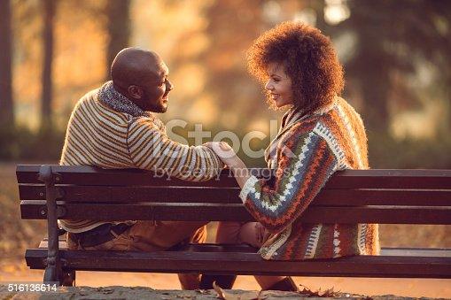 Loving African American couple talking to each other while sitting on bench in autumn park.