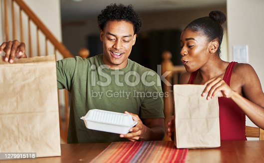istock african american couple sitting at table looking at food delivery 1279915118