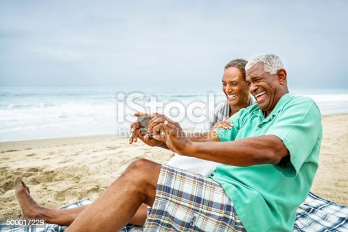A senior African American couple are sitting on a sandy beach, taking a selfie with a smart phone.  They are both smiling widely as they sit on a plaid blanket over beige sand.  There are white-green sea waters in the background that are topped with a blue-gray sky.