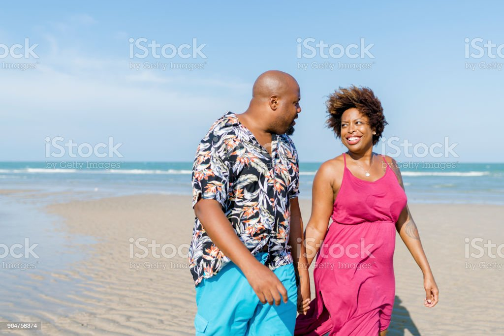 African American couple walking at the beach stock photo