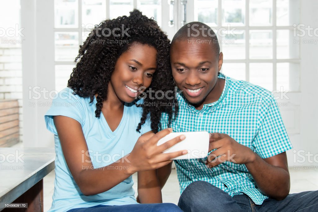 African american couple watching tv online on phone stock photo