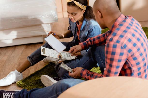 afrikanische amerikanische paar mit geld und budgetplanung in neue wohnung-rechner - geld schön verpacken stock-fotos und bilder