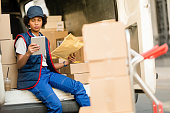 istock African American courier using digital tablet while checking packages in a van. 1185731127