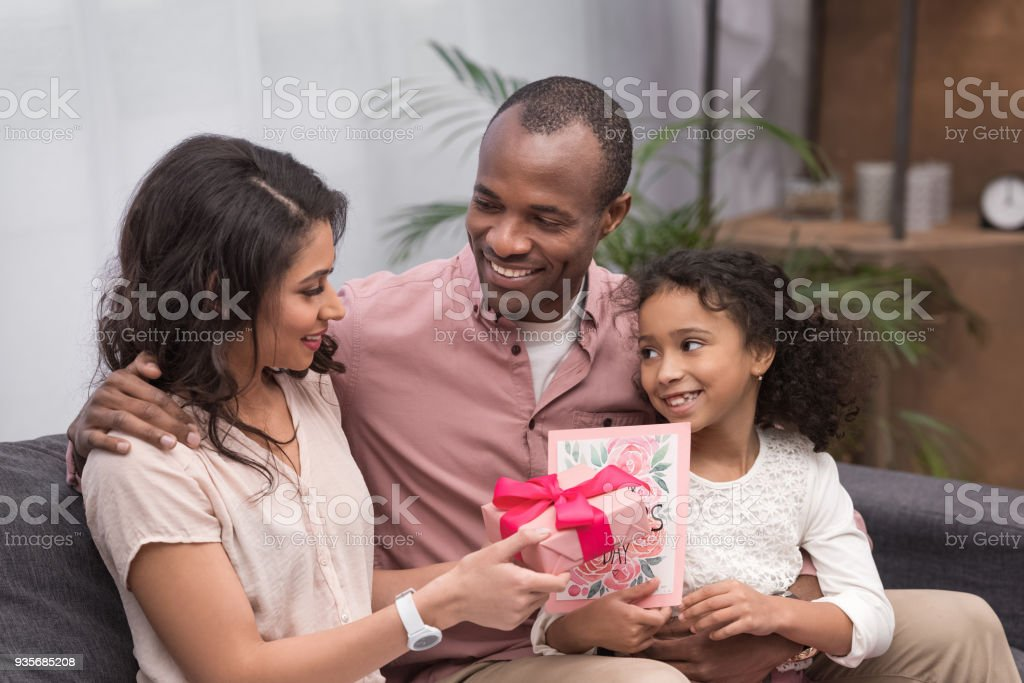 african american daughter and husband presenting gifts to wife on