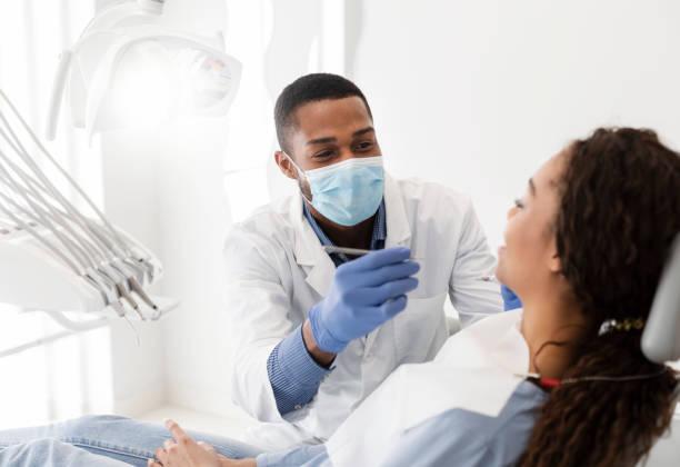 african american dentist making treatment in modern clinic - dentist zdjęcia i obrazy z banku zdjęć