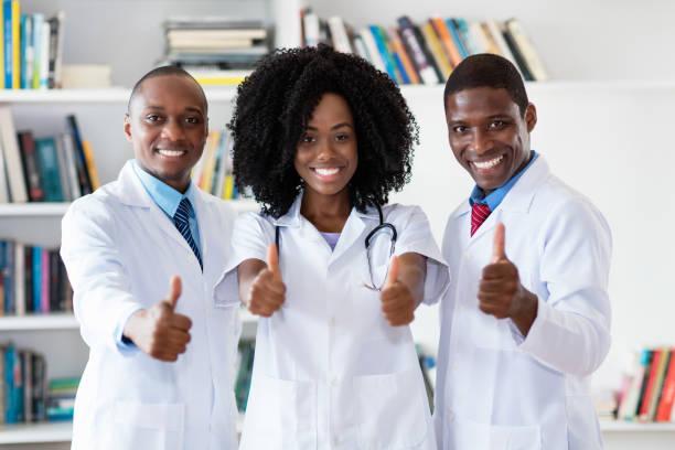 Médico afroamericano y médico general y enfermero como equipo médico - foto de stock