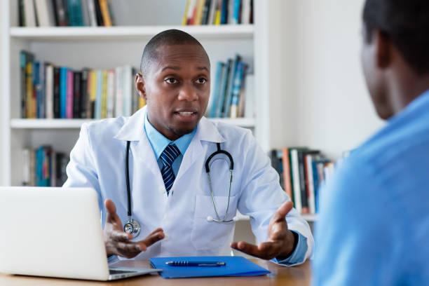 Médico afroamericano tiene malas noticias para el paciente masculino - foto de stock