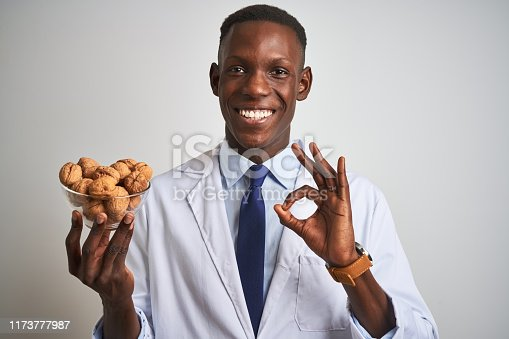 African american doctor man holding bowl with walnuts standing over isolated white background doing ok sign with fingers, excellent symbol
