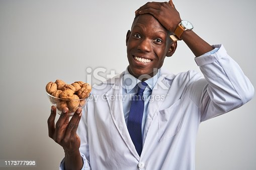 African american doctor man holding bowl with walnuts standing over isolated white background stressed with hand on head, shocked with shame and surprise face, angry and frustrated. Fear and upset for mistake.