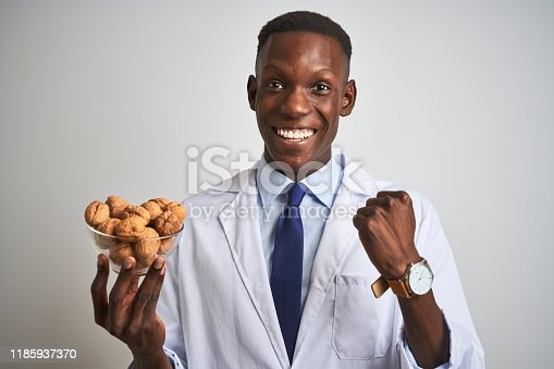 African american doctor man holding bowl with walnuts standing over isolated white background screaming proud and celebrating victory and success very excited, cheering emotion
