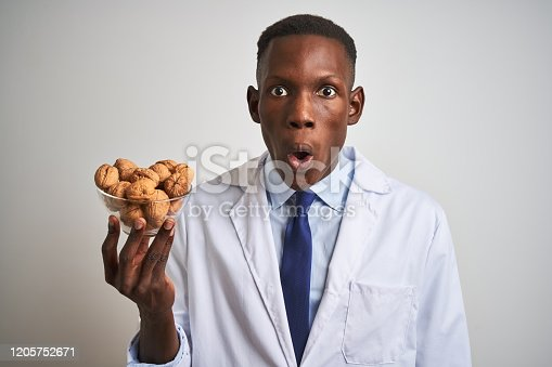 African american doctor man holding bowl with walnuts standing over isolated white background scared in shock with a surprise face, afraid and excited with fear expression