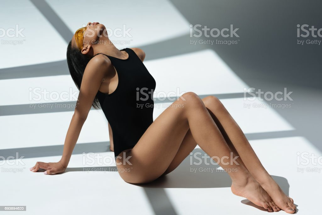 african american elegant sensual woman sunbathing in black swimsuit and protective goggles, on floor with shadows stock photo