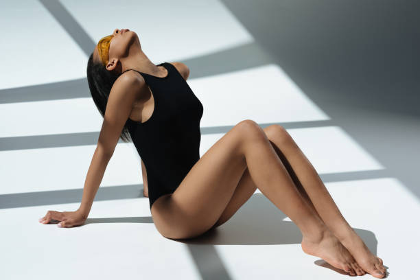 african american elegant sensual woman sunbathing in black swimsuit and protective goggles, on floor with shadows - leotard stock pictures, royalty-free photos & images