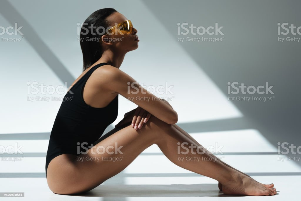 african american elegant woman in black bodysuit and protective goggles sunbathing stock photo