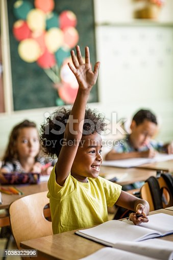 Happy black schoolgirl raising arm on a class in the classroom.