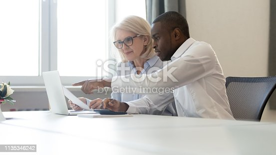 istock African american employee pointing at laptop discussing paperwork with colleague 1135346242