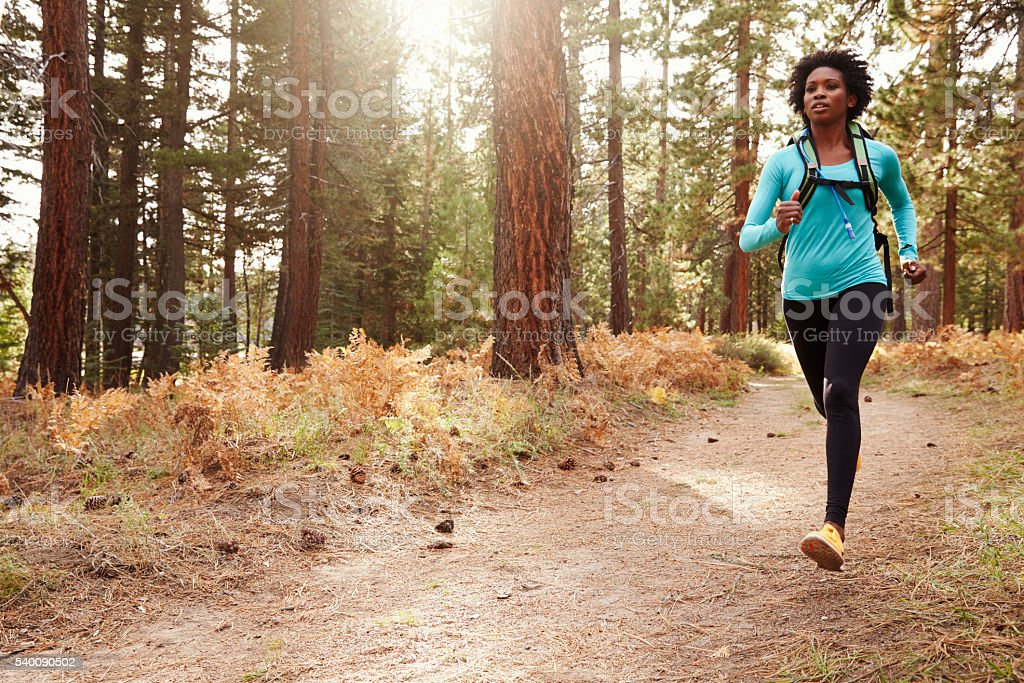 African American ethnicity woman running in a forest stock photo