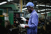 istock African american factory worker in using  laptop and push buttons to test the machine. 1268491434