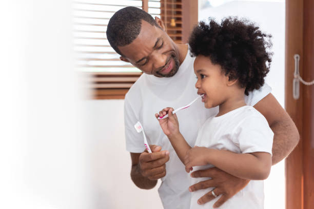 African American Family brushing teeth together stock photo