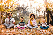 istock African American family doing Yoga relaxation exercises in autumn day. 1140942499