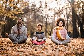 istock African American family doing Yoga relaxation exercises in autumn day. 1214441086