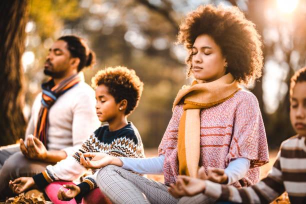 família afro-americana fazendo exercícios de relaxamento yoga no dia do outono. - meditation - fotografias e filmes do acervo