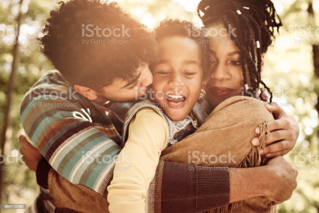 African American family enjoying in hug together in nature. royalty-free stock photo