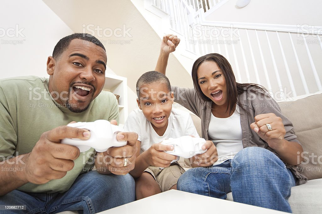 African American Family Having Fun Playing Computer Console Game stock photo