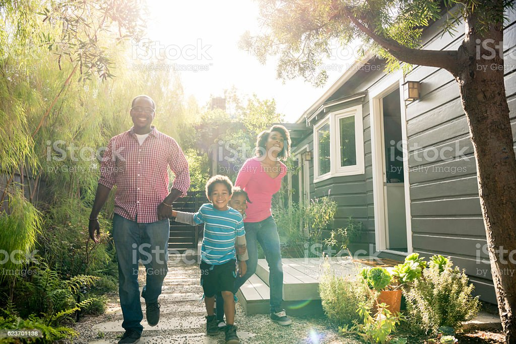 African American family holding hands in garden