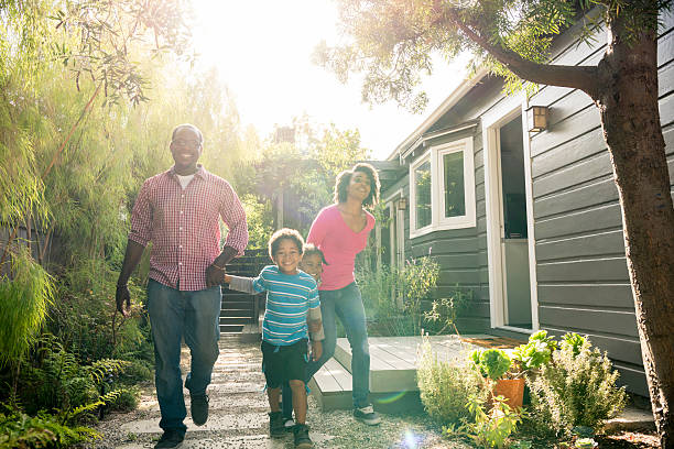 African American family holding hands in garden stock photo