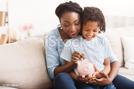 Money Saving Concept. Excited black mom and daughter putting coins into piggy bank, free space