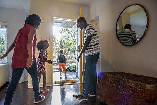 african american family leaving the house, father holding door - leaving stock photos and pictures