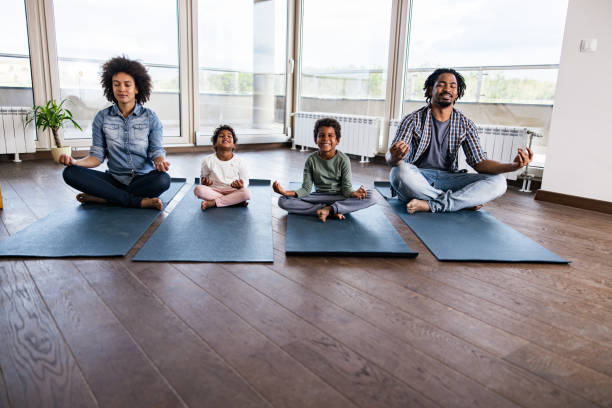 African American family meditating in Lotus position in the apartment. stock photo